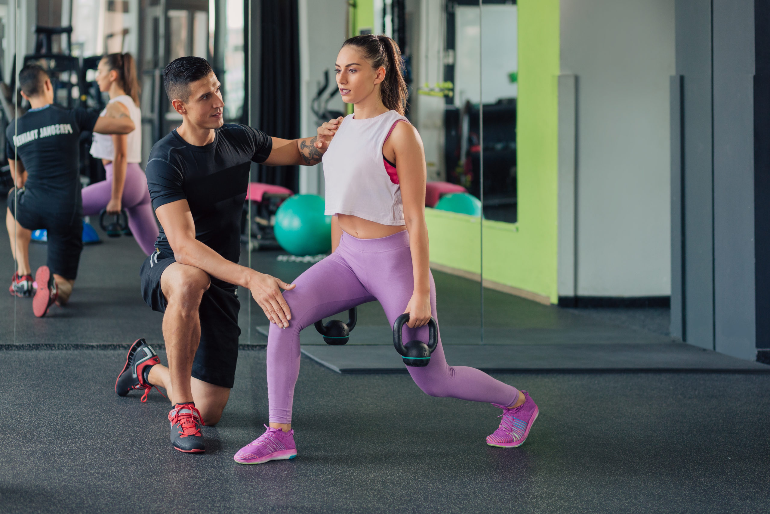 Young woman with male personal trainer in the gym doing kettlebell lunges